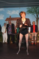 Teddy (Mike Smith) singing a show number in stockings and high heels. Don't ask.